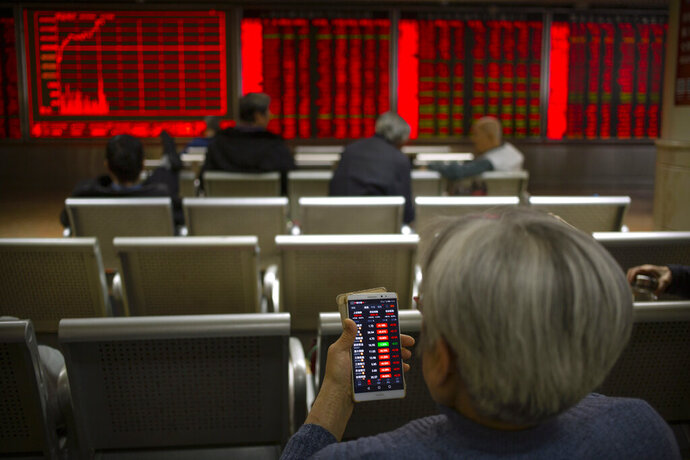 In this Tuesday, Nov. 19, 2019 photo, a Chinese investor uses a smartphone as she monitor stock prices at a brokerage house in Beijing. Shares retreated in Asia on Wednesday after Japan reported its worst monthly decline in exports in three years. (AP Photo/Mark Schiefelbein)
