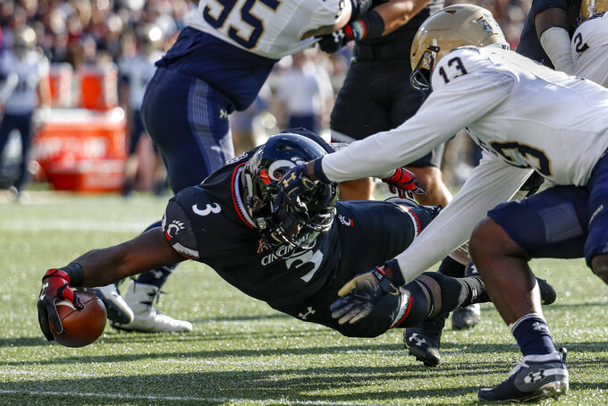 Cincinnati running back Michael Warren II (3) dives over the goal line for a touchdown against Navy safety Juan Hailey (13) in the first half of an NCAA college football game, Saturday, Nov. 3, 2018, in Cincinnati. (AP Photo/John Minchillo)