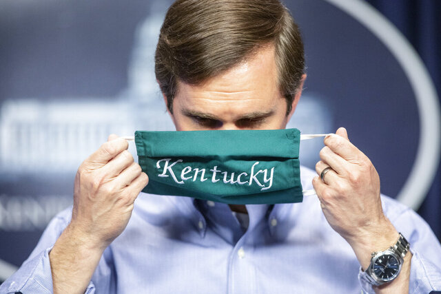 Kentucky Gov. Andy Beshear puts on a face mask after speaking to reporters at the Capitol in Frankfort, Ky., to provide an update on the coronavirus situation, Monday, May 11, 2020. (Ryan C. Hermens/Lexington Herald-Leader via AP)
