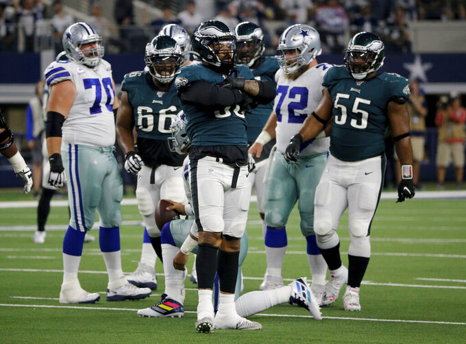 Philadelphia Eagles' Derek Barnett, center, celebrates after sacking Dallas Cowboys' Dak Prescott (4) as Akeem Spence (66) and Brandon Graham (55) look on in the first half of an NFL football game in Arlington, Texas, Sunday, Oct. 20, 2019. (AP Photo/Michael Ainsworth)