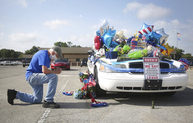 Dan Osborne prays at a makeshift memorial for Tulsa Police Officers Craig Johnson and Aurash Zarkeshan at Mingo Valley Division Tuesday, June 30, 2020. The officers were shot early Monday morning during a traffic stop.  (Mike Simons/Tulsa World via AP)