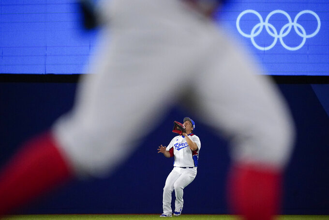 South Korea's Hyunsoo Kim looks catch a fly out hit by Dominican Republic's Melky Cabrera a baseball game at the 2020 Summer Olympics, Sunday, Aug. 1, 2021, in Yokohama, Japan. (AP Photo/Sue Ogrocki)