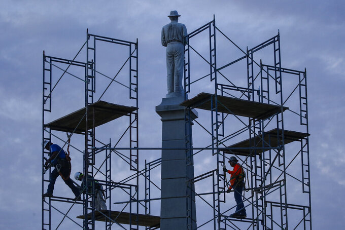 FILE - In this June 24, 2020, file photo, construction workers remove the final soldier statue, which sat atop The Confederate War Memorial in downtown Dallas. The Confederate battle flag is losing its place of official prominence in the South 155 years after the end of the Civil War and some Southern localities have removed memorials and statues dedicated to the Confederate cause. (Ryan Michalesko/The Dallas Morning News via AP, File)