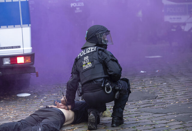 Police officers have arrested a man at the Weisestrasse in Berlin, Germany, where the bar 'Syndicate' is being evacuated on Friday, Aug. 7, 2020. Protesters have erected barricades and set several fires in a bid to stop Berlin police from evicting a left-wing bar that has been the focus of a campaign against gentrification. (Paul Zinken//dpa via AP)
