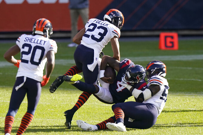 Houston Texans quarterback Deshaun Watson (4) is tackled by Chicago Bears' Kyle Fuller (23) and Danny Trevathan (59) during the first half of an NFL football game, Sunday, Dec. 13, 2020, in Chicago. (AP Photo/Nam Y. Huh)