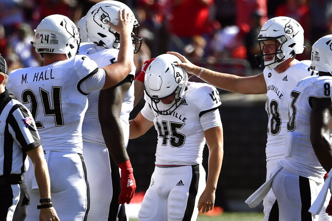 Louisville place kicker Blanton Creque (45) is congratulated by his teammates after making a field goal to put his team ahead during the second half of an NCAA college football game against Boston College in Louisville, Ky., Saturday, Oct. 5, 2019. Louisville won 41-39. (AP Photo/Timothy D. Easley)