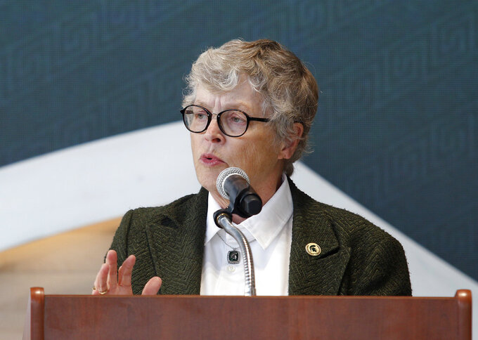 In this Oct. 20, 2017, photo, Michigan State University President Lou Anna Simon speaks during the dedication ceremony for the Gilbert Pavilion and Tom Izzo Hall of History inside Michigan State's Breslin Student Events Center in East Lansing, Mich. Simon submitted her resignation Wednesday, Jan. 24, 2018, amid an outcry over the school's handling of allegations against Larry Nassar. (AP Photo/Al Goldis, File)
