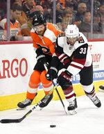 Philadelphia Flyers' Sean Couturier, left, and Arizona Coyotes' Alex Goligoski battle for position during the second period of an NHL hockey game, Thursday, Dec. 5, 2019, in Philadelphia. (AP Photo/Derik Hamilton)