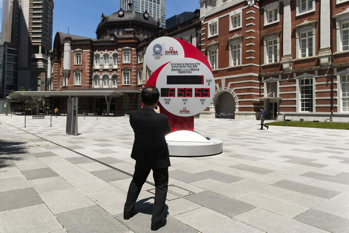 A man takes a picture of a countdown clock that shows seven more days to go before the opening ceremony of the Tokyo Olympic Games in Tokyo Friday, July 16, 2021. (AP Photo/Hiro Komae)