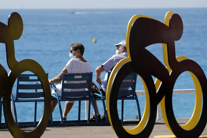 People sit next to an installation set up for the start of the 107th Tour de France cycling race, in the seafront of Nice, southern France, Thursday, Aug. 27, 2020. The Tour de France sets off shrouded in uncertainty and riding in the face of the coronavirus pandemic and mounting infections in France. (AP Photo/Christophe Ena)
