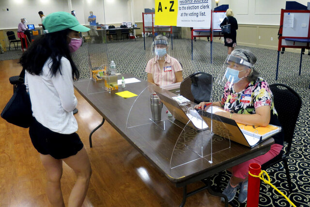Election workers Adonlie DeRoche, seated left, and Judy Smith, seated right, wear masks and face shields and work behind plexiglass for safety during the coronavirus pandemic, while assisting a voter during primary elections on Tuesday, July 14, 2020, in Portland, Maine. Voters were encouraged to vote ahead of time via absentee ballot, but polling stations were available for in-person voting. (AP Photo/David Sharp)