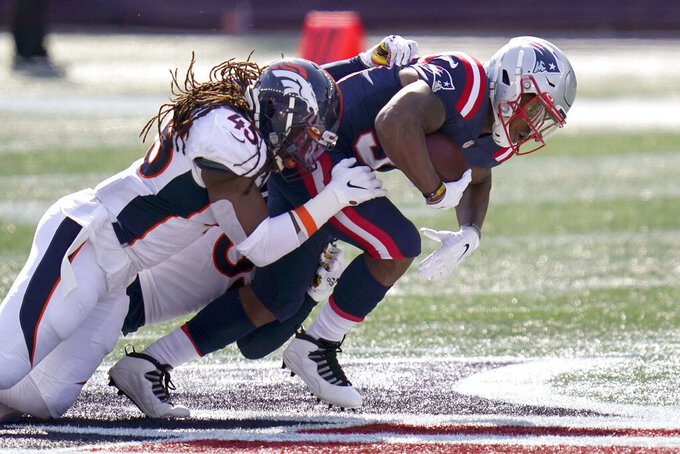 Denver Broncos linebacker Alexander Johnson, left, tackles New England Patriots running back Damien Harris in the first half of an NFL football game, Sunday, Oct. 18, 2020, in Foxborough, Mass. (AP Photo/Charles Krupa)
