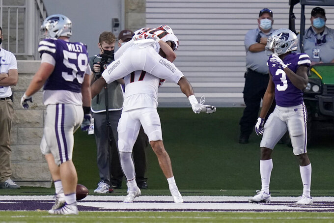 Oklahoma State wide receiver Brennan Presley (80) celebrates a touchdown with teammate Dillon Stoner (17) during the second half of an NCAA college football game against Kansas State in Manhattan, Kan., Saturday, Nov. 7, 2020. (AP Photo/Orlin Wagner)