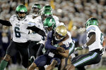 Navy quarterback Malcolm Perry (10) is brought down by a host of Tulane defenders, including safety Larry Brooks, center back, during the second half of an NCAA college football game, Saturday, Oct. 26, 2019, in Annapolis. Navy won 41-38. (AP Photo/Julio Cortez)