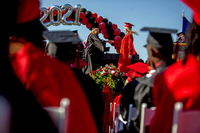 Grand Blanc senior Cassidy Young receives her diploma as more than 600 students graduate during one of two commencement ceremonies held on Thursday, June 3, 2021 at Frank Thomas Field in Grand Blanc, Mich. (Jake May/The Flint Journal via AP)