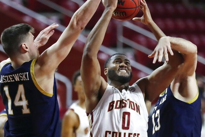 Boston College's Frederick Scott (0) shoots between Notre Dame's Nate Laszewski (14) and Nikola Djogo (13) during the second half of an NCAA college basketball game, Saturday, Feb. 27, 2021, in Boston. (AP Photo/Michael Dwyer)