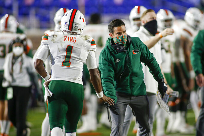 Miami coach Manny Diaz congratulates quarterback D'Eriq King (1) after a touchdown pass against Duke during the first quarter of an NCAA college football game Saturday, Dec. 5, 2020, in Durham, N.C. (Nell Redmond/Pool Photo via AP)