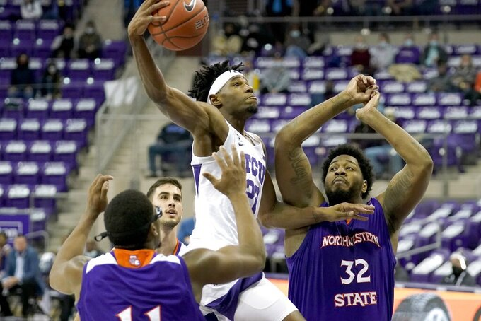 Northwestern State forward Jamaure Gregg, left, and center Larry Owens (32) defend as TCU guard RJ Nembhard (22) leaps to the basket for a shot during the second half of an NCAA college basketball game in Fort Worth, Texas, Thursday, Dec. 3, 2020. (AP Photo/Tony Gutierrez)