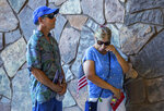 Tim Francone watches his wife, Karen Francone wipe tears from her eye as she listens during a memorial service for U.S. Marine Cpl. Hunter Lopez outside the Palm Springs Convention Center in Palm Springs, Calif., Saturday, Sept. 18, 2021. Mourners in California said prayers and their final goodbyes Saturday to three Marines killed in last month's bombing in Afghanistan. Lopez was part of a special crisis response team sent to provide security and help U.S. State Department officials evacuate thousands of Americans and Afghan refugees fleeing the Taliban as the 20-year war drew to a close. (Terry Pierson/The Orange County Register via AP)