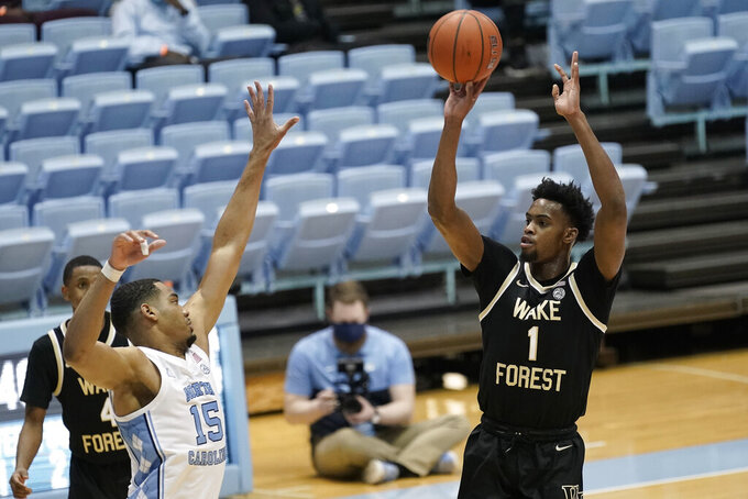 Wake Forest forward Isaiah Mucius (1) shoots while North Carolina forward Garrison Brooks (15) defends during the second half of an NCAA college basketball game in Chapel Hill, N.C., Wednesday, Jan. 20, 2021. (AP Photo/Gerry Broome)