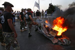 Lebanese retired soldiers burn tires, at a road linking to the parliament building where lawmakers and ministers are discussing the draft 2019 state budget, in Beirut, Lebanon, Thursday, July 18, 2019. Dozens of protesters have scuffled with Lebanese security guarding the country's parliament just as lawmakers met to vote on a controversial austerity budget. The protesters, most of them army veterans, have been camped near parliament for three days to oppose a draft bill that aims to cut into their pensions, among other measures to reduce public spending.(AP Photo/Hussein Malla)