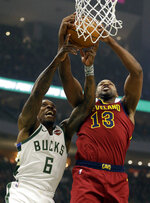 Milwaukee Bucks' Eric Bledsoe, left and Cleveland Cavaliers' Tristan Thompson reach for a rebound during the first half of an NBA basketball game Monday, Oct. 28, 2019, in Milwaukee. (AP Photo/Jeffrey Phelps)