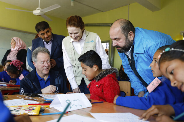 In this picture taken on March 3, 2020 and provided by UNICEF, UNICEF Executive Director Henrietta H. Fore, center, and WFP Executive Director, David Beasley, left, seated, interact with 3rd grade children, at Tal-Amara school, southern Idlib, Syria. Fore expressed hope in an interview with The Associated Press on Friday that a cease-fire that went into effect in Syria will hold so that children can return to normal life adding that nearly one third of Syria's children are out of school. Fore visited Syria this week where she met officials and toured villages on the edge of the northwestern province of Idlib. (Omar Sanadiki/UNICEF via AP )