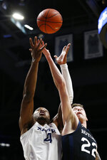 Xavier forward Tyrique Jones (4) and Butler forward Sean McDermott (22) reach for a rebound during the first half of an NCAA college basketball game Saturday, March 7, 2020, in Cincinnati. (AP Photo/Gary Landers)