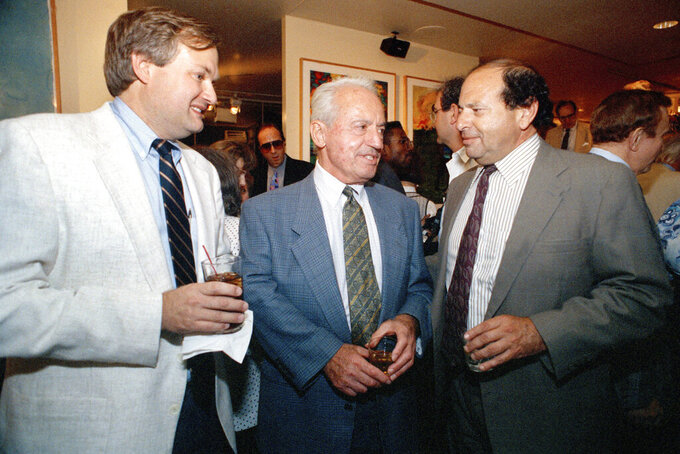 """FILE - In this July 1, 1991, file photo, Marvin Miller, center, the first executive director of the Major League Baseball Players Association, Donald Fehr, left, then the current head, and Richard Moss, right, celebrate the 25th anniversary of the MLBPA, and the publication of the book, """"A Whole New Ballgame"""" by Miller and Allen Barra in New York. Ahead of Miller's induction Wednesday into the Hall of Fame, union leaders say his philosophies and strategies still make up the union's foundation.  (AP Photo/Peter Morgan, File)"""