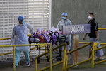 Health workers receive a new patient suspected of COVID-19 arriving at the University Hospital of Brasília, in Brasilia, Brazil, Wednesday, Aug. 5, 2020. (AP Photo/Eraldo Peres)