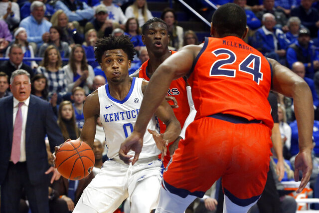 Kentucky's Ashton Hagans, left, looks for an opening against Auburn's Anfernee McLemore (24) during the first half of an NCAA college basketball game in Lexington, Ky., Saturday, Feb. 29, 2020. (AP Photo/James Crisp)