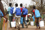 In this photo taken on Tuesday Feb.12, 2019, former child soldiers walk home after receiving materials and supplies during a child soldier release in Yambio, South Sudan. An estimated 19,000 child soldiers are in South Sudan, one of the highest rates in the world, according to the United Nations. As the country emerges from civil war, some worry the fighting could re-ignite if former child soldiers aren't properly reintegrated into society.  (AP Photo/Sam Mednick)