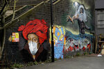 A mural by street artist Lionel Stanhope with a face mask reference to coronavirus next to one of his other works, at right, painted on a bridge wall in Ladywell, south east London, Thursday, April 2, 2020. (AP Photo/Matt Dunham