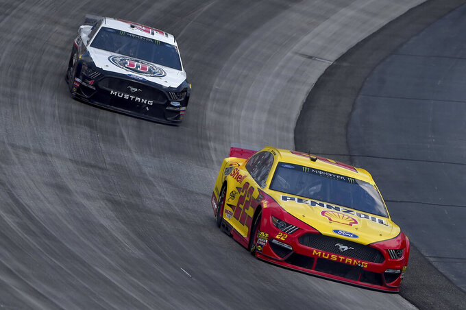 Joey Logano (22) leads Kevin Harvick (4) during the NASCAR Cup Series auto race, Monday, May 6, 2019, at Dover International Speedway in Dover, Del. (AP Photo/Will Newton)