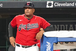 """Cleveland Indians' Sandy Alomar Jr. waits to walk on the field during a baseball game against the Kansas City Royals, Tuesday, Sept. 21, 2021, in Cleveland. On Sunday, one of the American League's charter members will play its final home game of 2021, and also its last at Progressive Field as the Indians, the team's name since 1915, when """"Shoeless"""" Joe Jackson was the starting right fielder on opening day. Much more than a late-season matchup against the Chicago White Sox, the home finale will signify the end of one era and beginning of a new chapter for the team, which will be called the Cleveland Guardians next season. (AP Photo/Tony Dejak)"""