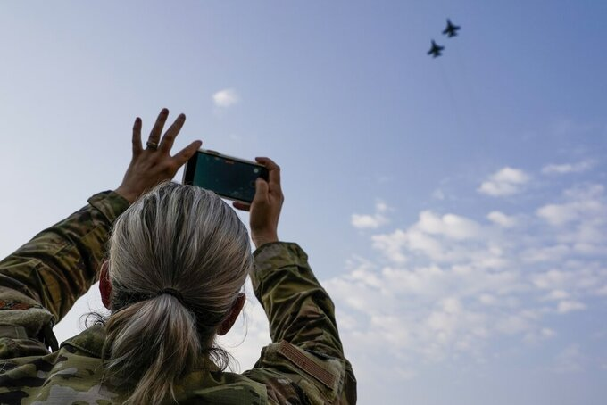 Cpt. Leslie Westmont of the 115th Fighter Wing takes pictures of a fly over before an NCAA college football game between Wisconsin and Eastern Michigan Saturday, Sept. 11, 2021, in Madison, Wis. (AP Photo/Morry Gash)
