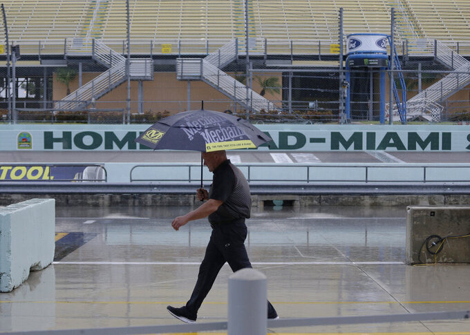 A crew member walks in the pits during a rain delay of NASCAR auto racing activities on Friday, Nov. 15, 2019, at Homestead-Miami Speedway in Homestead, Fla. (AP Photo/Terry Renna)