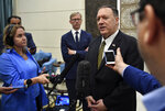 U.S. Secretary of State Mike Pompeo speaks to the media before departing from al-Bateen Air Base in Abu Dhabi, United Arab Emirates, Thursday, Sept. 19, 2019, as U.S. special representative on Iran Brian Hook, left, listens. (Mandel Ngan/Pool via AP)