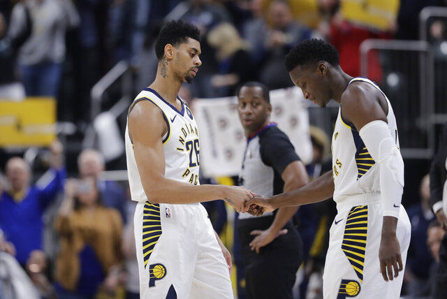 Indiana Pacers' Jeremy Lamb (26) shakes hands with Victor Oladipo as Oladipo enters during the first half of the team's NBA basketball game against the Chicago Bulls, Wednesday, Jan. 29, 2020, in Indianapolis. (AP Photo/Darron Cummings)