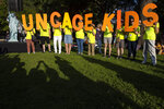 File - In this July 12, 2019, file photo, protesters hold up a sign that reads 'uncage kids' during a rally in Lafayette Park near the White House where they were calling for and end to immigrant children's detention and family separations. The U.S. government didn't have the technology needed to properly document and track the thousands of immigrant families separated at the southern border in 2018. That's according to a new report by an internal government watchdog. (AP Photo/Jon Elswick, File)