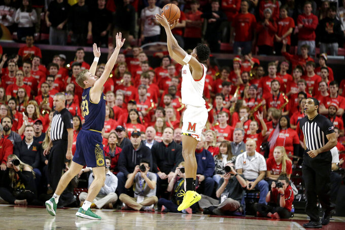 Maryland guard Aaron Wiggins, right, shoots against Notre Dame guard Dane Goodwin during the first half of an NCAA college basketball game, Wednesday, Dec. 4, 2019, in College Park, Md. (AP Photo/Julio Cortez)