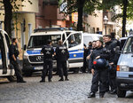 Police officers are standing at the Weisestrasse in Berlin, Germany, where the bar 'Syndicate' is being evacuated on Friday, Aug. 7, 2020. Protesters have erected barricades and set several fires in a bid to stop Berlin police from evicting a left-wing bar that has been the focus of a campaign against gentrification. (Paul Zinken//dpa via AP)