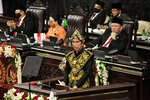 Indonesian President Joko Widodo, wearing a traditional outfit, delivers his national address before the parliament members in Jakarta, Indonesia, Friday, Aug. 14, 2020. Indonesia's president called on all citizens to turn the COVID-19 crisis into an advancement opportunity and pledged health care reforms in an address Friday ahead of the country's 75th anniversary of independence. (AP Photo)