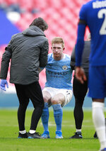 Manchester City's Kevin De Bruyne stands up helped by medical staff after injuring during the English FA Cup semifinal soccer match between Chelsea and Manchester City at Wembley Stadium in London, England, Saturday, April 17, 2021. (AP Photo/Ian Walton, Pool)