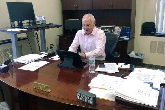 In this Monday, Dec. 30, 2019, photo, Mark Ojakian, president of the Connecticut State Colleges and Universities system, works at his office in Hartford, Conn. Ojakian is pressing ahead with a plan to consolidate the state's 12 community colleges by 2023, despite opposition from some professors and staff. (AP Photo/Susan Haigh)