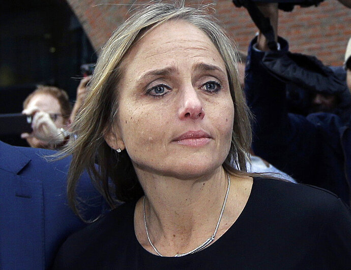 FILE - In this April 25, 2019 file photo, district court judge Shelley M. Richmond Joseph departs federal court in Boston after facing obstruction of justice charges for allegedly helping a man in the country illegally evade immigration officials as he left her Newton, Mass., courthouse after a 2018 hearing. The state Supreme Judicial Court reversed course Tuesday, Aug. 13, and ruled that Joseph, who has been suspended, can collect her annual salary and ordered her to receive back pay dating to late April. (AP Photo/Steven Senne, File)