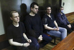 Members of the New Greatness group, who are charged with the organization of an extremist association, sit behind a glass in a courtroom prior to a court hearing in Moscow, Russia, Tuesday, July 14, 2020. Russian authorities on Tuesday demanded prison terms for three members of a youth group charged with creating an extremist organization, in a case that elicited public outraged and has been seen as politically motivated. (AP Photo/Pavel Golovkin)