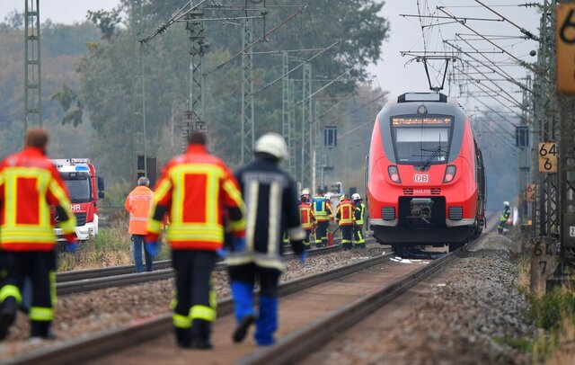 Rescue workers are on duty at the scene of a train accident in Bruckberg, Germany, Tuesday, Oct. 13, 2020. Two teenager brothers were hit and killed by a train in Bavaria on Tuesday as they apparently ran across the tracks in an attempt to make their own connection, police said. (Matthias Balk/dpa via AP)