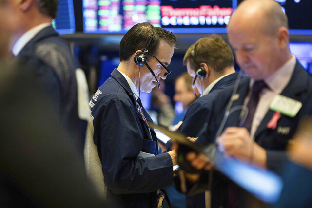 This photo provided by the New York Stock Exchange, Thursday, March 19, 2020, shows trader Gregory Rowe, center, as he works on the trading floor. Stocks are see-sawing between gains and losses in midday trading on Wall Street Thursday, but the moves are more subdued than the wild jabs that have dominated recent weeks. (NYSE Photo by Alyssa Ringler via AP)