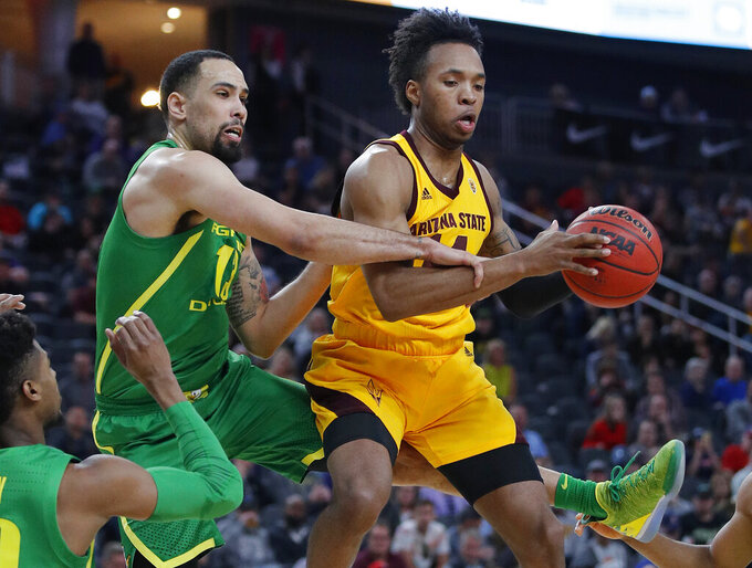 Arizona State's Kimani Lawrence, right, grabs a rebound over Oregon's Paul White during the first half of an NCAA college basketball game in the semifinals of the Pac-12 men's tournament Friday, March 15, 2019, in Las Vegas. (AP Photo/John Locher)